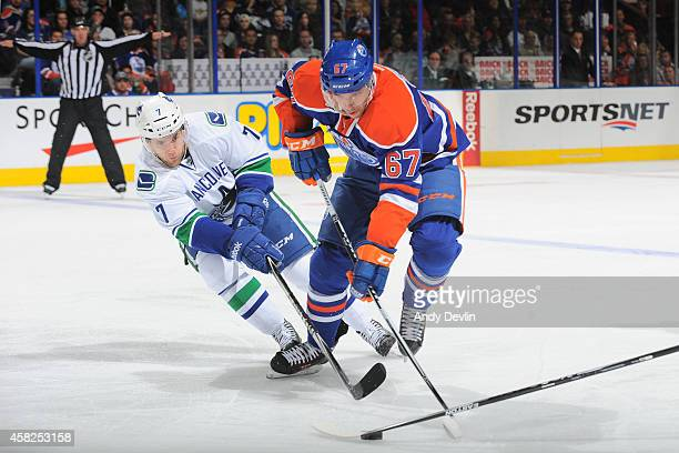 Linden Vey of the Vancouver Canucks pursues Benoit Pouliot of the Edmonton Oilers on November 1 2014 at Rexall Place in Edmonton Alberta Canada