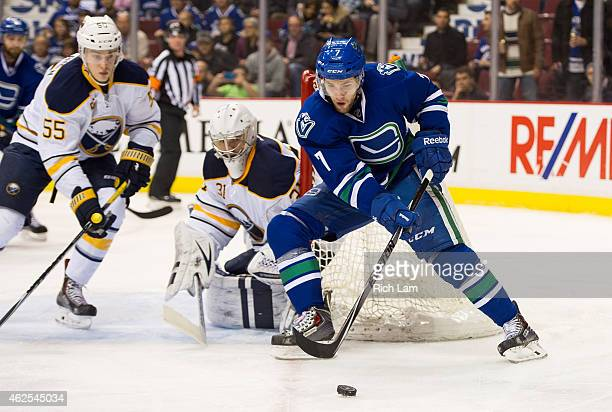 Linden Vey of the Vancouver Canucks tries to get a shot on goalie Matt Hackett of the Buffalo Sabres as Rasmus Ristolainen help defend on the play in...