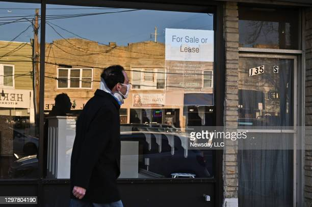 Person walks past a vacated storefront along Wellwood Avenue in Lindenhurst, New York on January 7, 2021 during the coronavirus pandemic. A sign in...