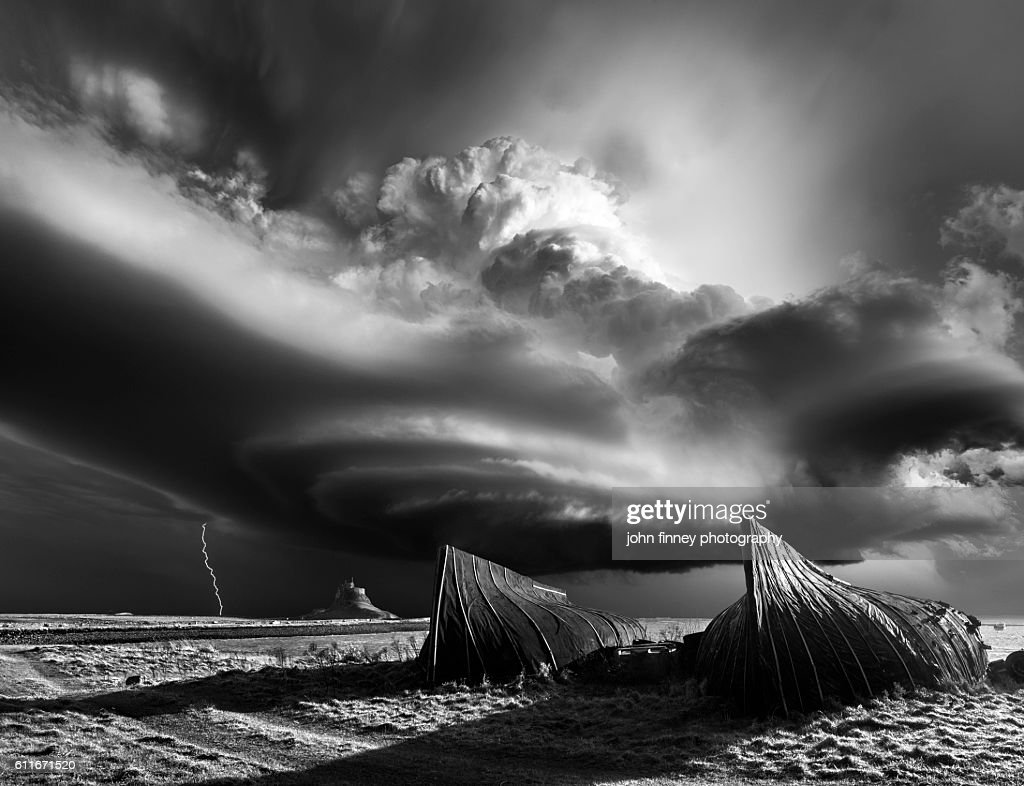 Lindisfarne Castle in Northumberland with a monster supercell thunderstorm in dramatic black and white. : Stock Photo