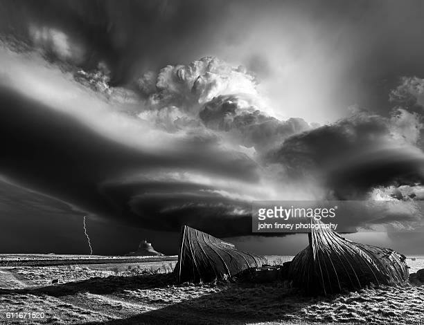 Lindisfarne Castle in Northumberland with a monster supercell thunderstorm in dramatic black and white.