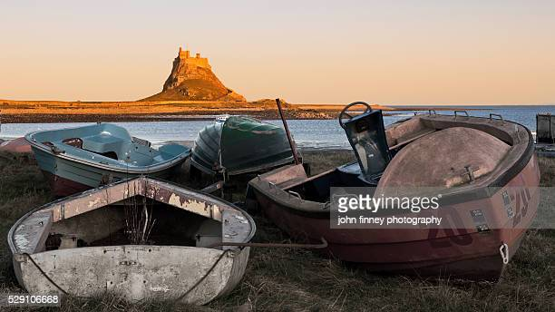 Lindisfarne Castle with old boats at sunset. Northumberland. UK. Europe.
