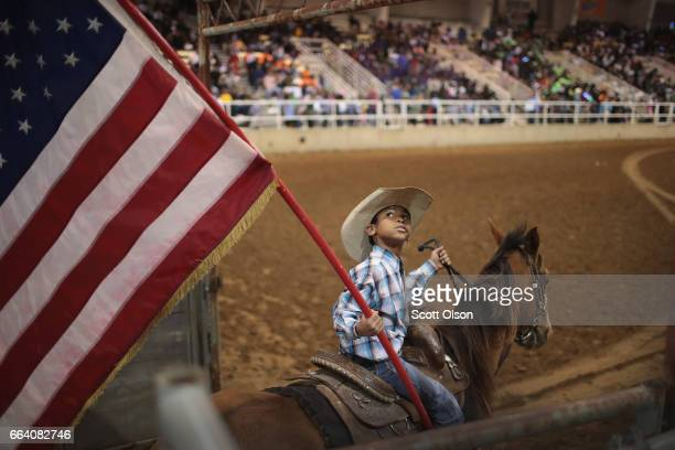 Lindon Demery carries the flag into the arena before the start of competition at the Bill Pickett Invitational Rodeo on March 31 2017 in Memphis...