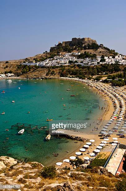 lindos beach and acropolis - lindos stock photos and pictures
