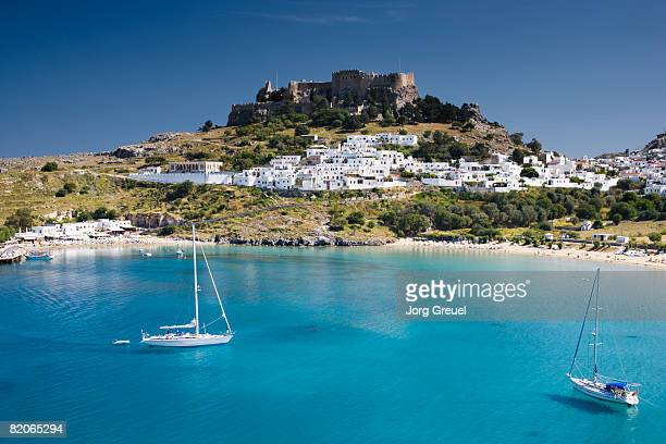 lindos with beach + acropolis - lindos stock photos and pictures