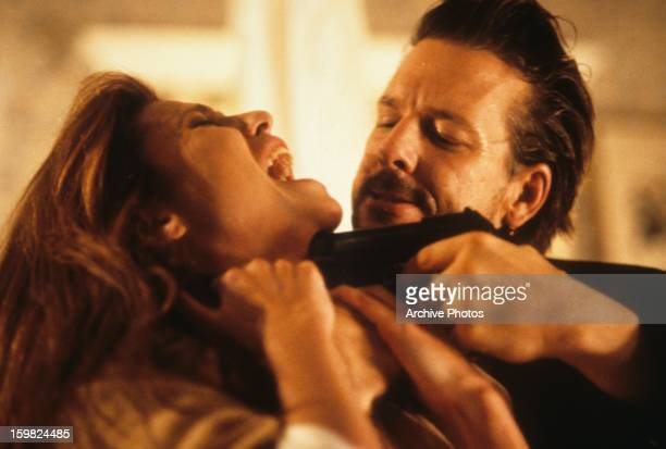 Lindsay Crouse has a gun held against her throat by Mickey Rourke in a scene from the film 'Desperate Hours' 1990