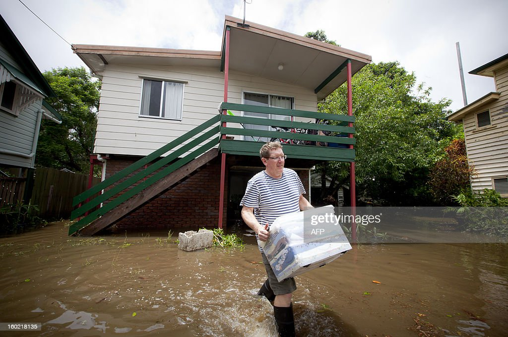 Lindsay Enright walks through floodwaters as he starts the clean up operation outside his Cullen Street home, in the inner Brisbane suburb of Newmarket on January 28, 2013. Helicopters plucked dozens of stranded Australians to safety in dramatic rooftop rescues on January 28 as severe floods swept the northeast, killing three people and inundating thousands of homes. AFP PHOTO / Patrick HAMILTON