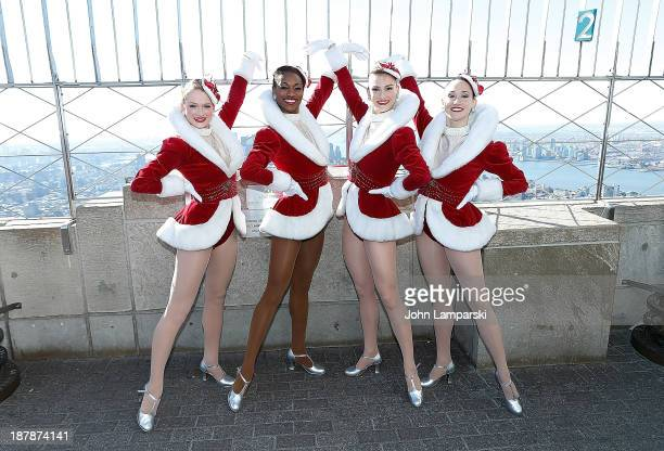 Lindsay Howe Kali Grinder Kim Petros and Jennifer Laroche of the Radio City Rockettes light the Empire State Building green red in celebration of the...