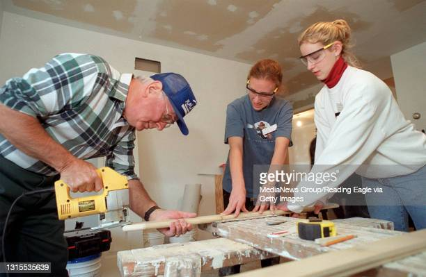 Lindsay L. Haman of Whitfield, a director for Reading-Berks Habitat for Humanity, uses a jigsaw to cut some trim at the organization's Luzerne Street...