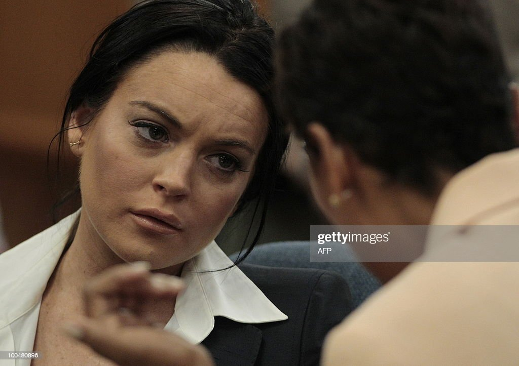 Lindsay Lohan (L) talks with her lawyer
