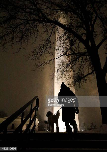 Lindsay Sorensen walks her dog Casper in the swirling snow at the Bunker Hill Monument in Charlestown