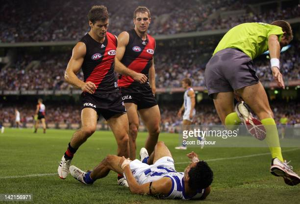 Lindsay Thomas of the Kangaroos collides with a line umpire during the round one AFL match between the North Melbourne Kangaroos and the Essendon...