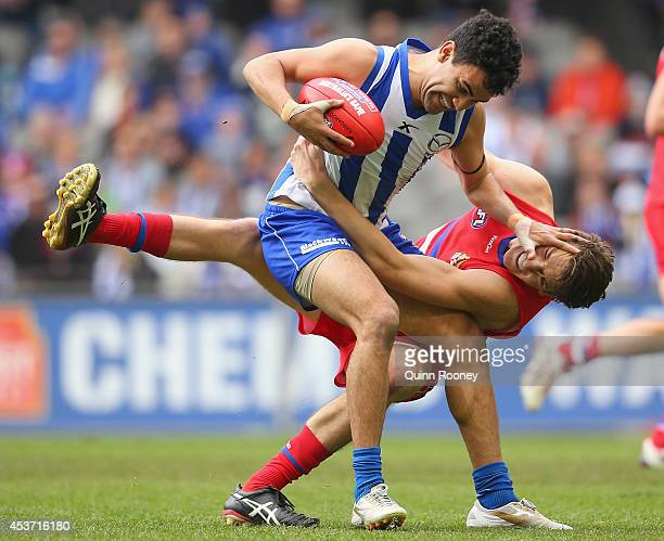 Lindsay Thomas of the Kangaroos fends off a tackle by Marcus Bontempelli of the Bulldogs during the round 21 AFL match between the North Melbourne...