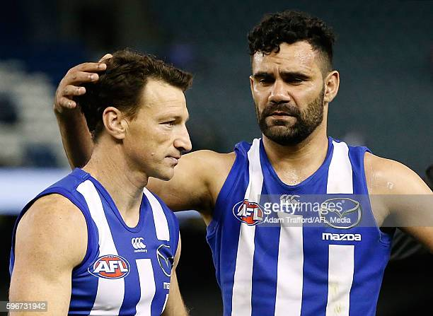 Lindsay Thomas of the Kangaroos hugs teammate Brent Harvey of the Kangaroos during the 2016 AFL Round 23 match between the North Melbourne Kangaroos...