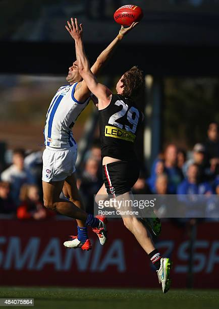 Lindsay Thomas of the Kangaroos is challenged by Jimmy Webster of the Saints during the round 20 AFL match between the North Melbourne Kangaroos and...