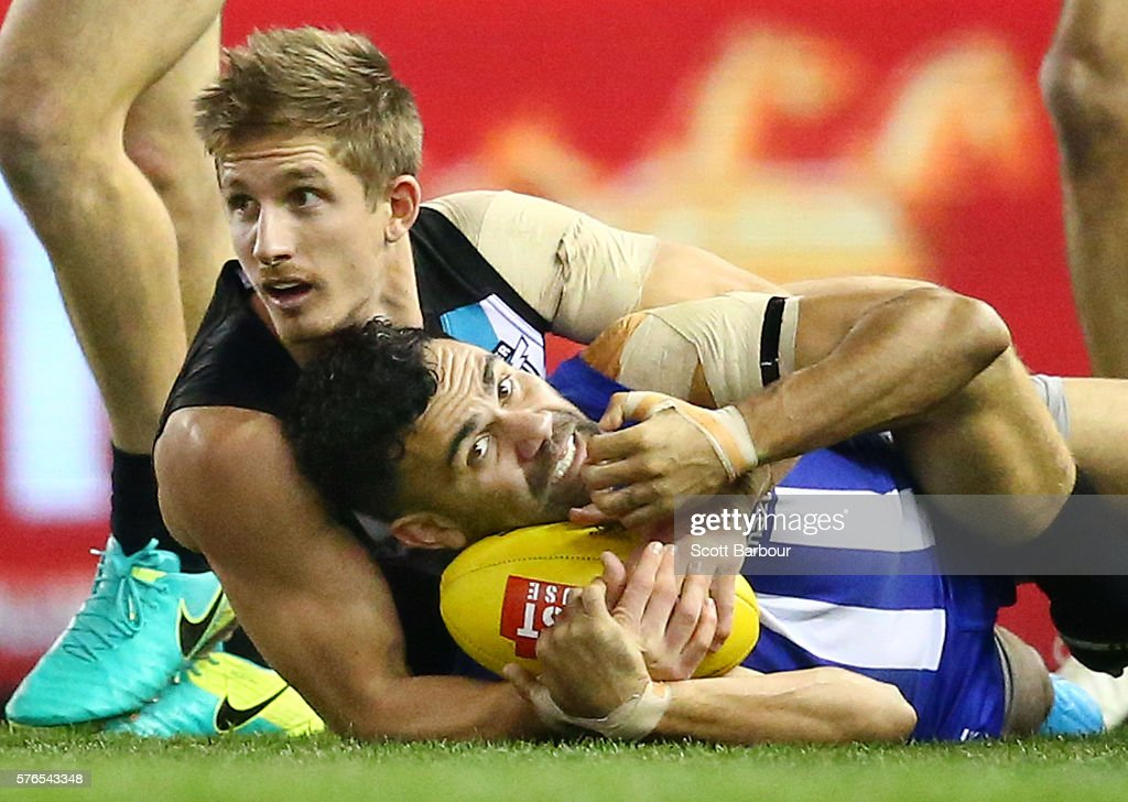 Lindsay Thomas of the Kangaroos is tackled by Hamish Hartlett of the Power in a high tackle and is awarded a free kick during the round 17 AFL match between the North Melbourne Kangaroos and the Port Adelaide Power at Etihad Stadium on July 16, 2016 in Melbourne, Australia.