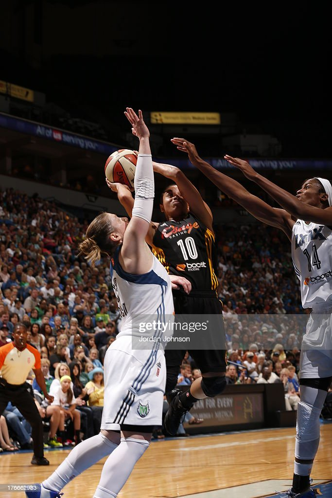 Lindsay Whalen #13 and Devereaux Peters #14 of the Minnesota Lynx attempt to block Angel Goodrich #10 of the Tulsa Shock during the WNBA game on August 16, 2013 at Target Center in Minneapolis, Minnesota.