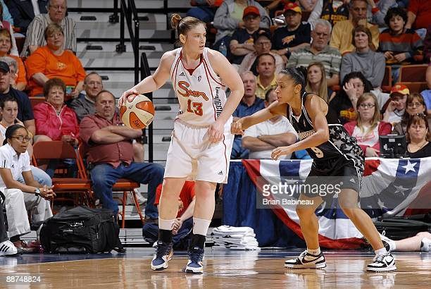 Lindsay Whalen of the Connecticut Sun drives the ball against Edwige LawsonWade of the San Antonio Silver Stars during the WNBA game on June 21 2009...