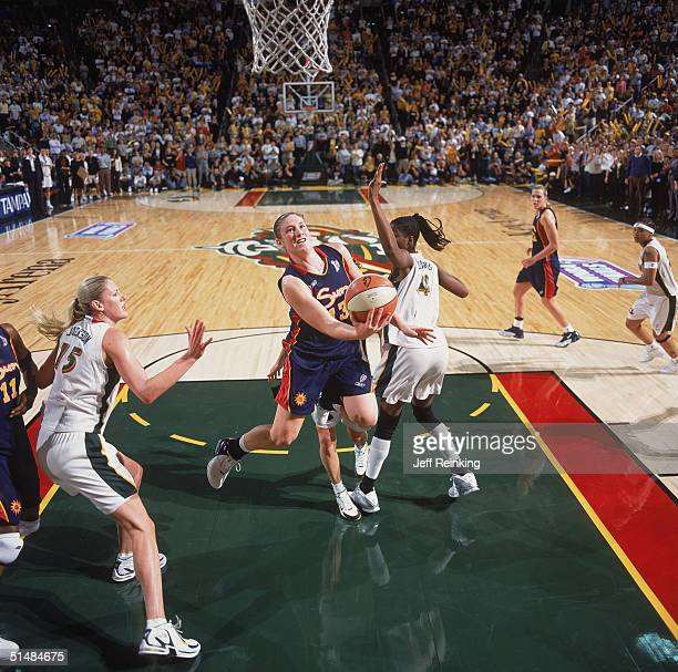 Lindsay Whalen of the Connecticut Sun drives to the basket against Simone Edwards of the Seattle Storm in Game three of the WNBA Finals on October 12...