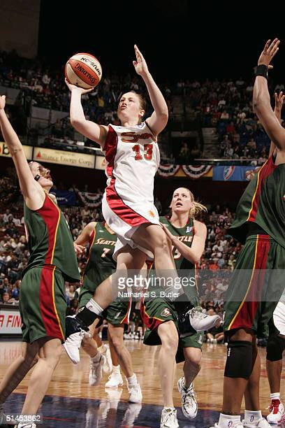 Lindsay Whalen of the Connecticut Sun shoots against Sue Bird of the Seattle Storm during Game 1 of the 2004 WNBA Finals on October 8, 2004 at...
