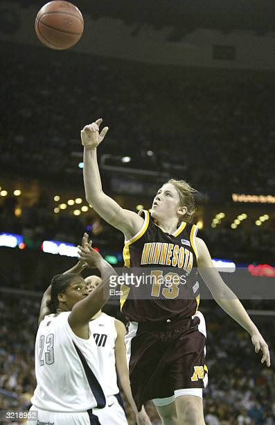 Lindsay Whalen of the Minnesota Golden Gophers shoots over Willnett Crockett of the University of Connecticut Huskies during the semifinal game of...