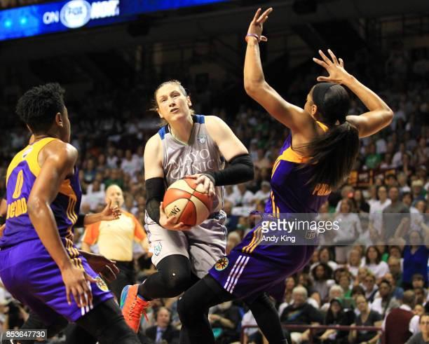 Lindsay Whalen of the Minnesota Lynx drives on Alana Beard of the Los Angeles Sparks and Candace Parker of the Los Angeles Sparks during the fourth...