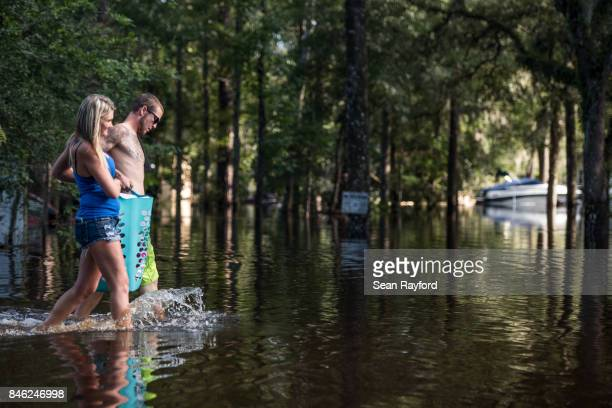 Lindsey Brown left and Christian Treadwell evacuate their neighborhood inundated by flood waters caused by Hurricane Irma September 12 2017 in...