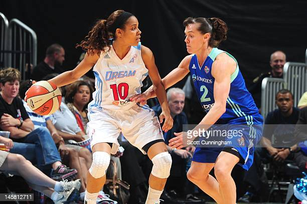 Lindsey Harding of the Atlanta Dream handles the ball against Kelly Miller of the New York Liberty at Philips Arena on May 25 2012 in Atlanta Georgia...