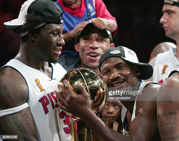 Lindsey Hunter and Ben Wallace of the Detroit Pistons hold the Larry O'Brien NBA Championship trophy after defeating the Los Angeles Lakers in game...