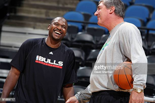 Lindsey Hunter of the Chicago Bulls catches up with Assistant Coach Bill Laimbeer of the Minnesota Timberwolves before the preseason game on October...