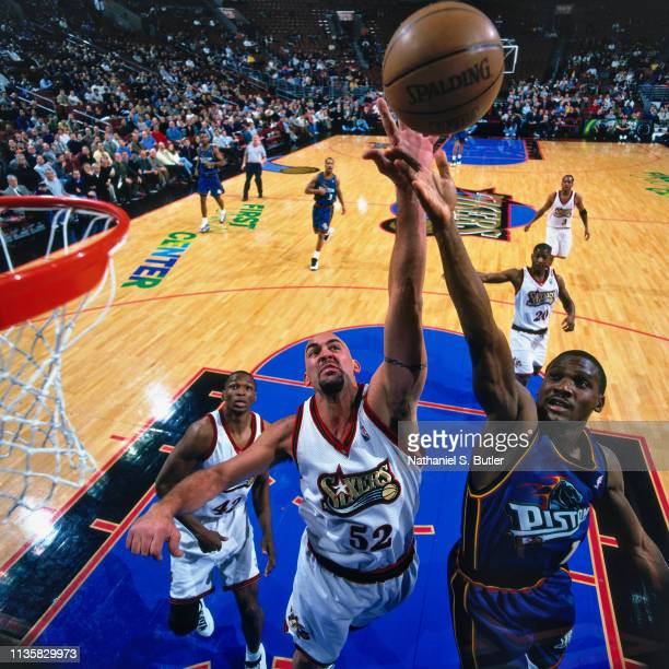 Lindsey Hunter of the Detroit Pistons goes up for a shot against Matt Geiger of Philadelphia 76ers on February 9 1999 at the First Union Center in...