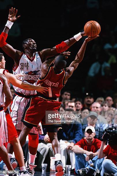 Lindsey Hunter of the Detroit Pistons shoots against Hakeem Olajuwon of the Houston Rockets during the game on February 15 2000 at Compaq Center in...