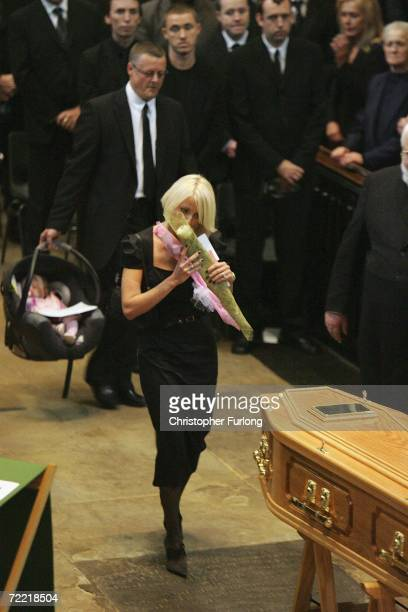 Lindsey Hunter the wife of snooker star Paul Hunter kisses a rose before placing it on his coffin during his funeral at Leeds Parish Church on...