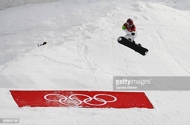 Lindsey Jacobellis of the United States grabs her board during the jump before her fall in the Womens Snowboard Cross Final on Day 7 of the 2006...