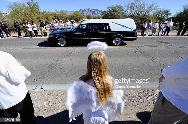 Lindsey Lummus wearing an angels wings and a halo watches as the funeral hearse carrying the casket of nineyearold Christina Taylor Green arrives at...