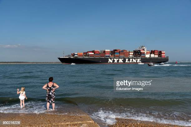 MYK Line Arcadia a container ship on Southampton Water off Calshot Spit southern England UK People on the shingle beach at Calshot