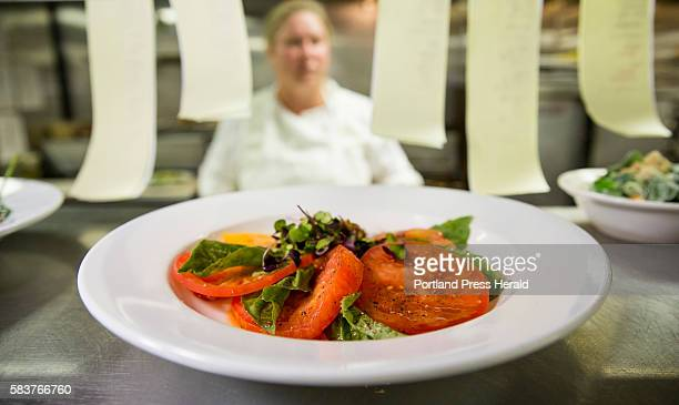 Line cook reads new meal tickets at the Woodlands Club kitchen in Falmouth after plaing this tomato caprese salad with pistachioencrusted goat cheese