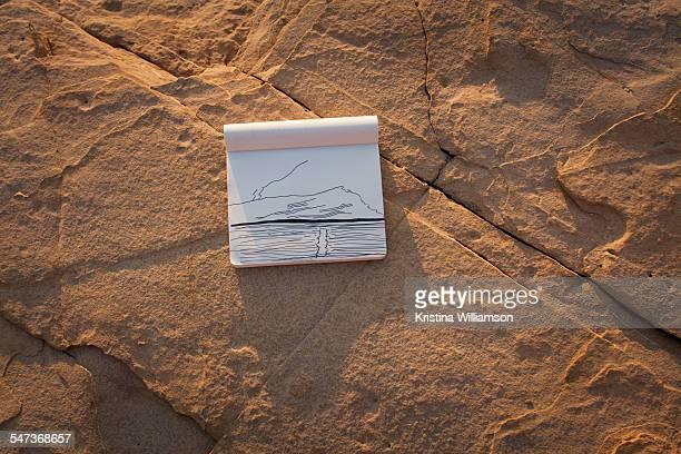 Line drawing of seascape in sketchbook on rocks