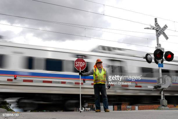 Line flagger Chris Dugent holds a stop sign as the train passes at Steele Street on Tuesday June 19 2018