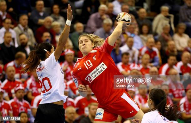 Line Jorgensen of Denmark challenges Mouna Chebbah of Tunisia during the IHF Women's Handball World Championship group C match between Denmark and...