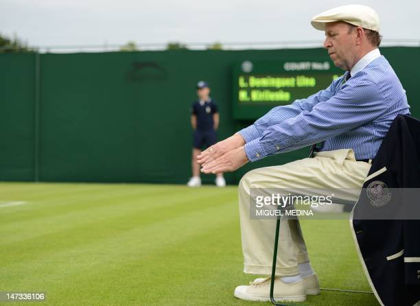 A line judge indicates that a ball is out on day three of the 2012 Wimbledon Championships tennis tournament at the All England Tennis Club in...