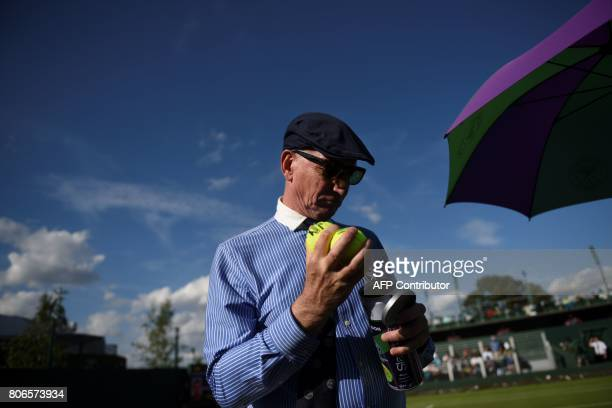 A line judge inspects a tube of balls at The All England Lawn Tennis Club in Wimbledon southwest London on July 3 2017 on the first day of the 2017...