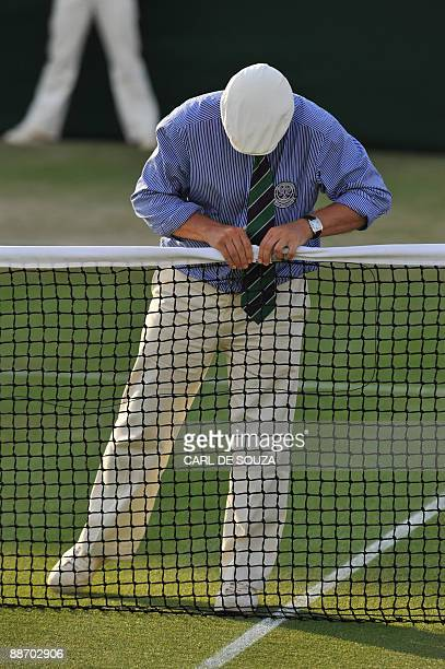 Line judge inspects the net during play between Spain's Tommy Robredo and Israel's Dudi Sela during their third round match in the 2009 Wimbledon...