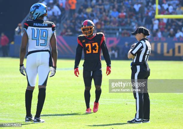 Line judge Maia Chaka stands on the field with tight end Donald Parham of the Dallas Renegades and running back Dujuan Harris of the Los Angeles...