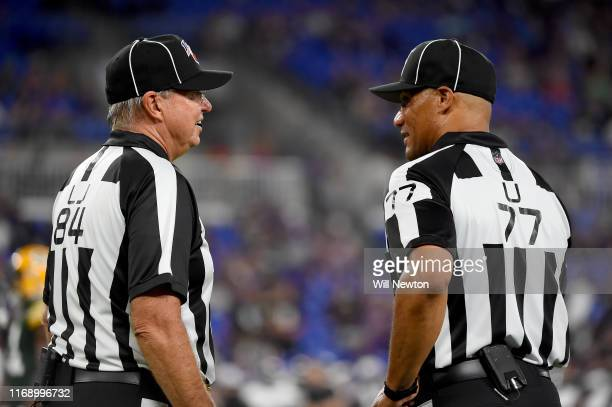 Line judge Mark Steinkerchner and referee Terry McAulay speak during the second half of a preseason game between the Baltimore Ravens and the Green...