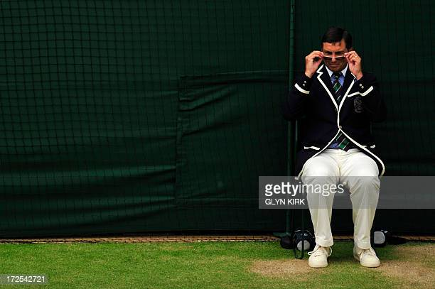 A line judge peers over his glasses as Spain's David Ferrer plays against Argentina's Juan Martin Del Potro during their men's singles quarterfinal...