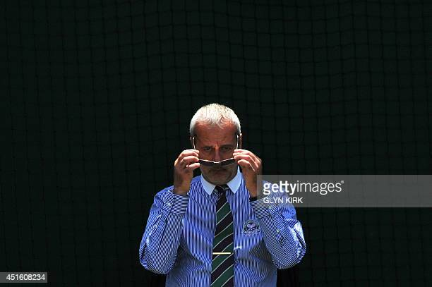 A line judge puts on his sunglasses during the men's singles quarterfinal match between Serbia's Novak Djokovic and Croatia's Marin Cilic on day nine...