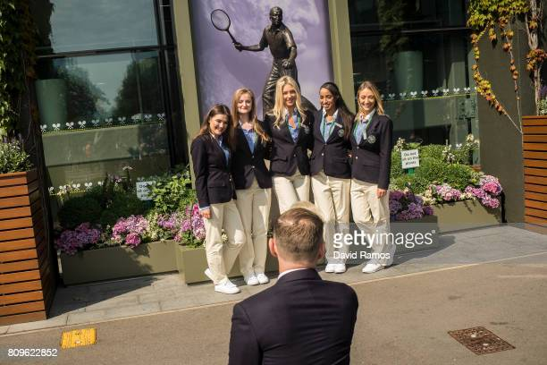 Line Judges pose for a picture in front of the statue of Fred Perry on day four of the Wimbledon Lawn Tennis Championships at the All England Lawn...