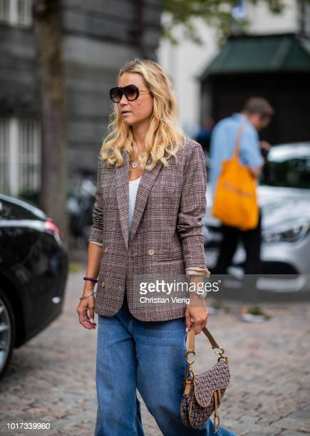 Line Langmo wearing flared denim jeans checked blazer Dior saddle bag seen outside Michael Olestad during Oslo Runway SS19 on August 15 2018 in Oslo...