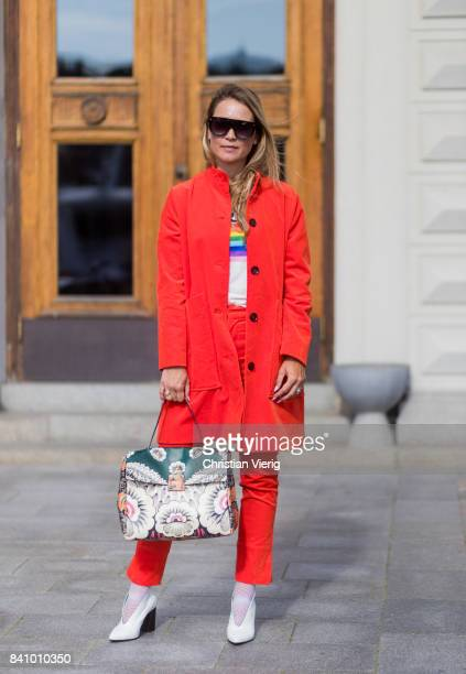 Line Langmo wearing red Ganni jacket and pants white tshirt with rainbow print outside Stylein on August 30 2017 in Stockholm Sweden